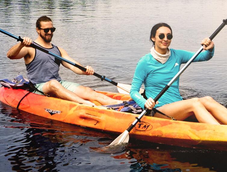 Two kayakers paddling on water